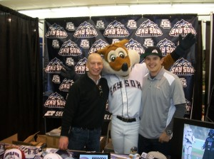 Director of Corporate Sales Chris Phillips and Group Sales Manager Drew Trujillo pose with Sox in front of the Sky Sox booth at the Home and Landscaping Show.